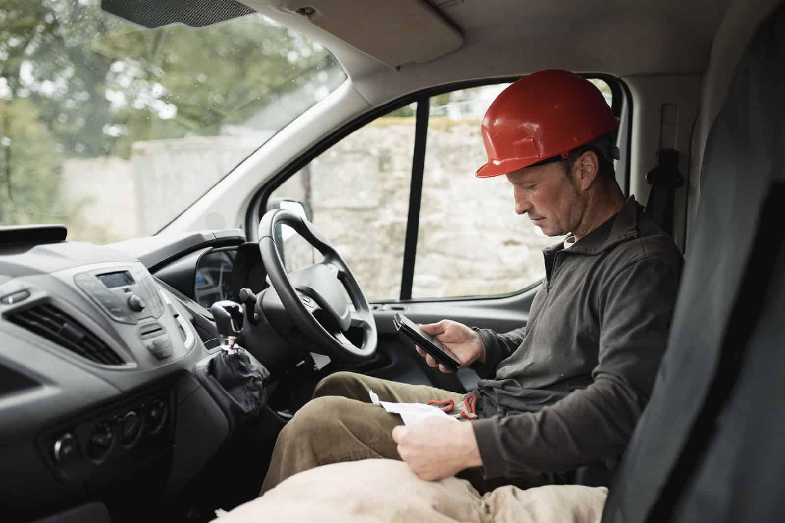 Man in vehicle checking phone